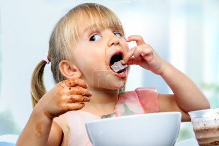 Little girl eating chocolate breakfast.