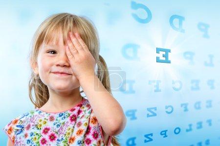 Little girl reading eye chart.