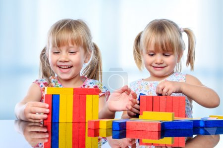 Kids building with wooden blocks at table.