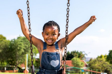 Happy African kid raising arms on swing