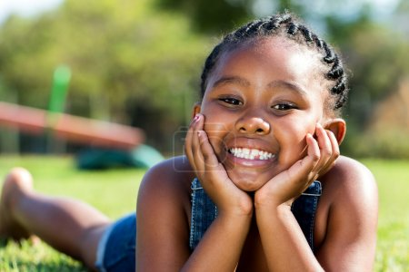 Cute african girl laying on green grass