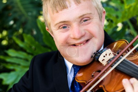Photo for Close up portrait of young man with down syndrome playing violin. Handicapped boy violinist in suit isolated against green background. - Royalty Free Image