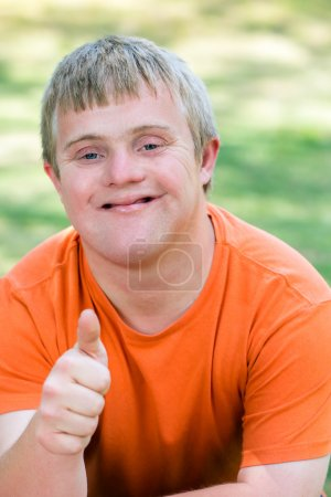 Photo for Close up portrait of friendly young man with down syndrome in orange t-shirt gesturing thumb up sign - Royalty Free Image