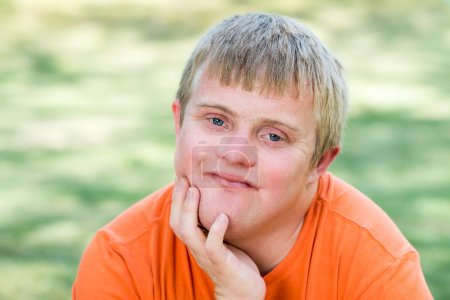 Photo for Close up outdoor portrait of Handsome blue-eyed boy with down syndrome. - Royalty Free Image