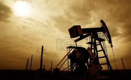 Oil and gas well profiled on dramatic sky