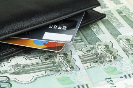 Photo pour Deux cartes de crédit dans un portefeuille noir sur les roubles russes . - image libre de droit