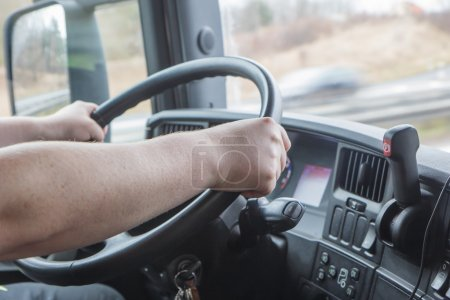 Closeup view of the hands of truck driver who is holding the steering wheel. Photo shooted in the vehicle cabin.