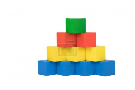 Photo for Pyramid built from wooden colorful cubes on an isolated white background. Bottom line consists of blue cubes over which there are three yellow cubes over which there are two red cubes on top is green cube. Front view - Royalty Free Image