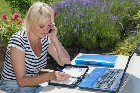 Blonde middle aged woman is sitting outdoors. She ...