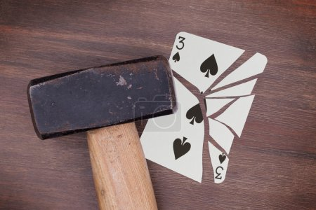 Hammer with a broken card, three of spades