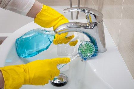 Housemaid cleaning a bathroom