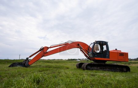 Excavator working  on a field