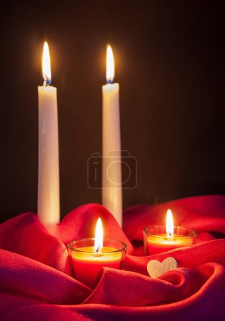 Beautiful candles on red cloth
