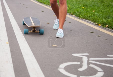 Girl skating on a longboard outdoors