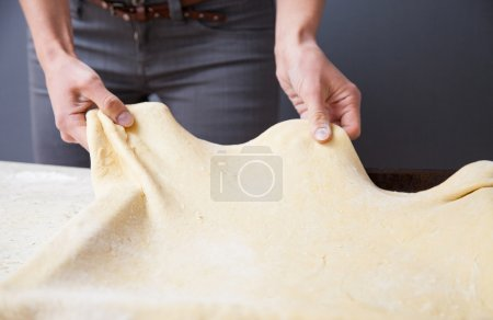 Woman's hands stretching dough