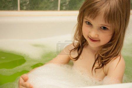 Charming little girl has a bath