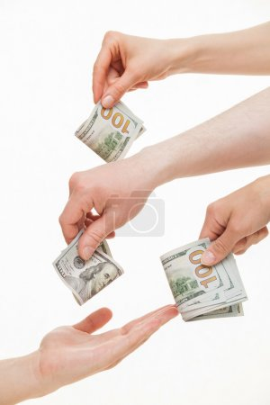 Several hands put dollars in empty palm
