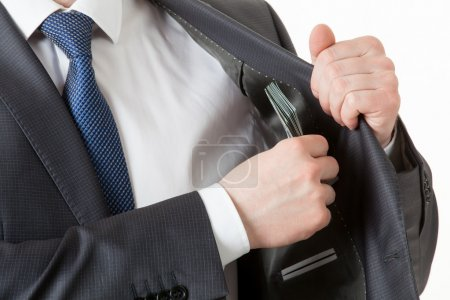 Businessman holding putting dollars in a pocket