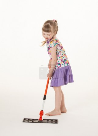 Girl learning to hold a mop
