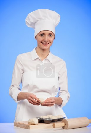 Smiling woman cook making tasty cakes