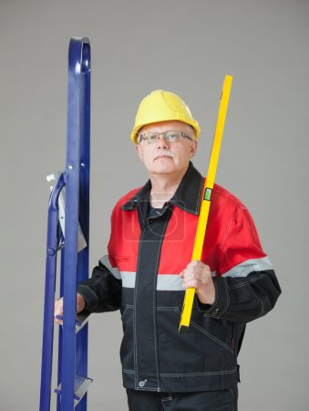 Builder holding a ladder and a level