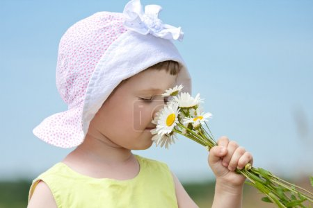 Girl smelling bunch of flowers