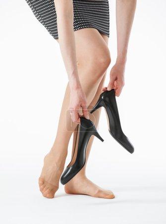 Photo pour Jeune femme tenant ses chaussures noires sur fond blanc - image libre de droit