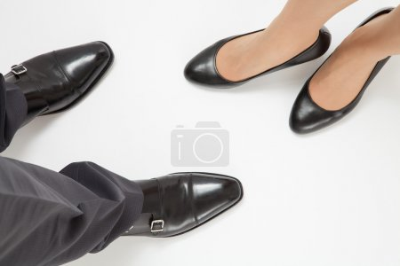 Photo for Close-up of businessman's and businesswoman's legs on white floor - Royalty Free Image