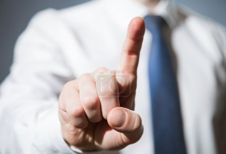 Photo for Businessman touching with index finger something, gray background - Royalty Free Image