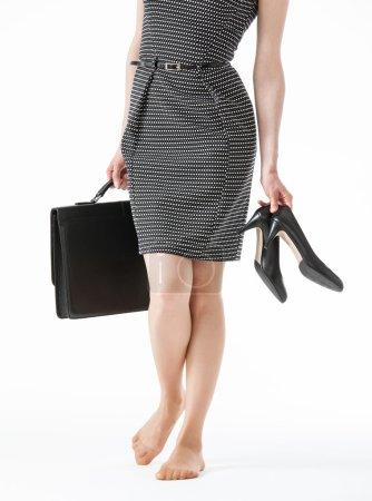 Photo pour Jeune femme tenant ses chaussures noires et une mallette sur fond blanc - image libre de droit
