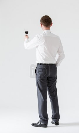 businessman holding goblet of wine
