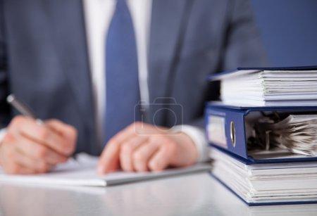Photo pour Homme d'affaires, signer des documents, fond bleu - image libre de droit