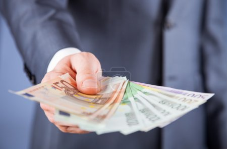 Businessman's hand reaching out euro banknotes