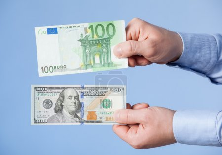 Businessman comparing hundred dollars and hundred euro
