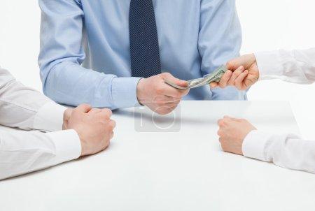 Boss giving dollars to collaborator