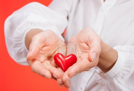 Female hands holding a ceramic heart