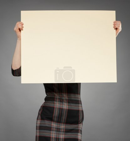 Attractive young woman holding poster
