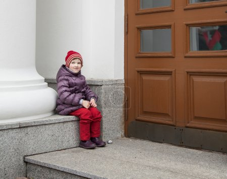 Child sitting near a historical building