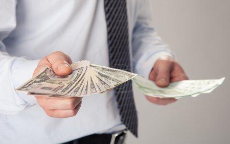 Businessman's hands proposing banknotes
