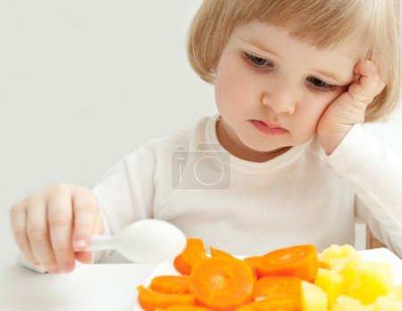 upset girl with vegetables