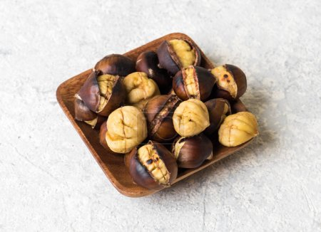 Photo for Roasted chestnut. Grilled chestnuts on wooden plate - Royalty Free Image