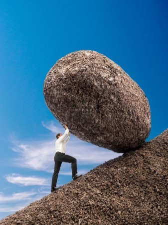 Photo pour Homme d'affaires retroussant énorme rocher sur une pente sur ciel bleu - image libre de droit