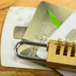 Combination lock and credit cards on wood board....