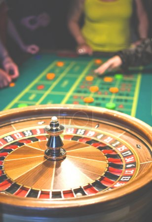 Roulette in motion. Green table with colored chips ready to play