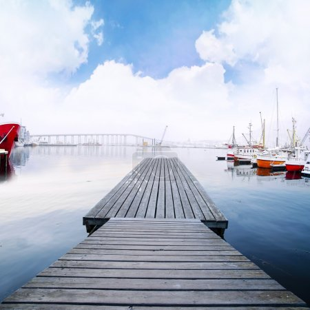 Wood footbridge dock in harbor with boats and beautiful cloudscape