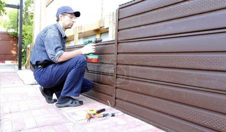 Worker installs plastic siding on the facade of the house