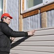 A worker installs panels beige siding on the facad...