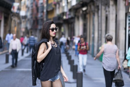 Casual young woman walking on the street, urban lifestyle.