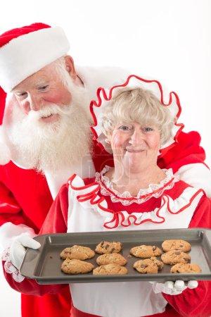 Photo pour Mme Claus rayonne tout en tenant un plateau de biscuits sur un plateau, frais du four. Père Noël regarde avec excitation par-dessus son épaule les biscuits chauds frais - image libre de droit