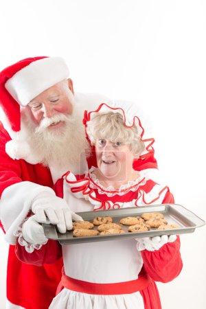 Photo pour Le Père Noël vole un cookie chaud dans le plateau de Mme Claus . - image libre de droit